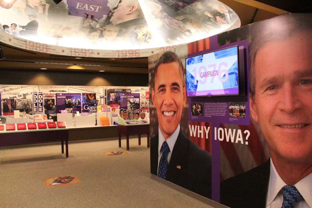 The smiling faces of the nation's last two president look on a visitors enter the First In The Nation exhibit at the State Historical Museum. Photo By Katie Ramsey